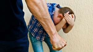 мужчина избивает мальчика