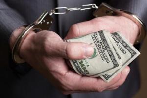 руки с деньгами в наручниках